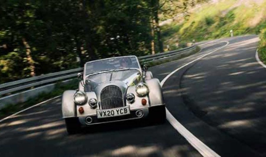 Silbernes britisches Auto in einer Kurve